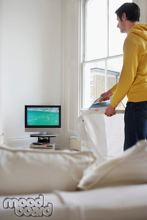 Man ironing and watching television