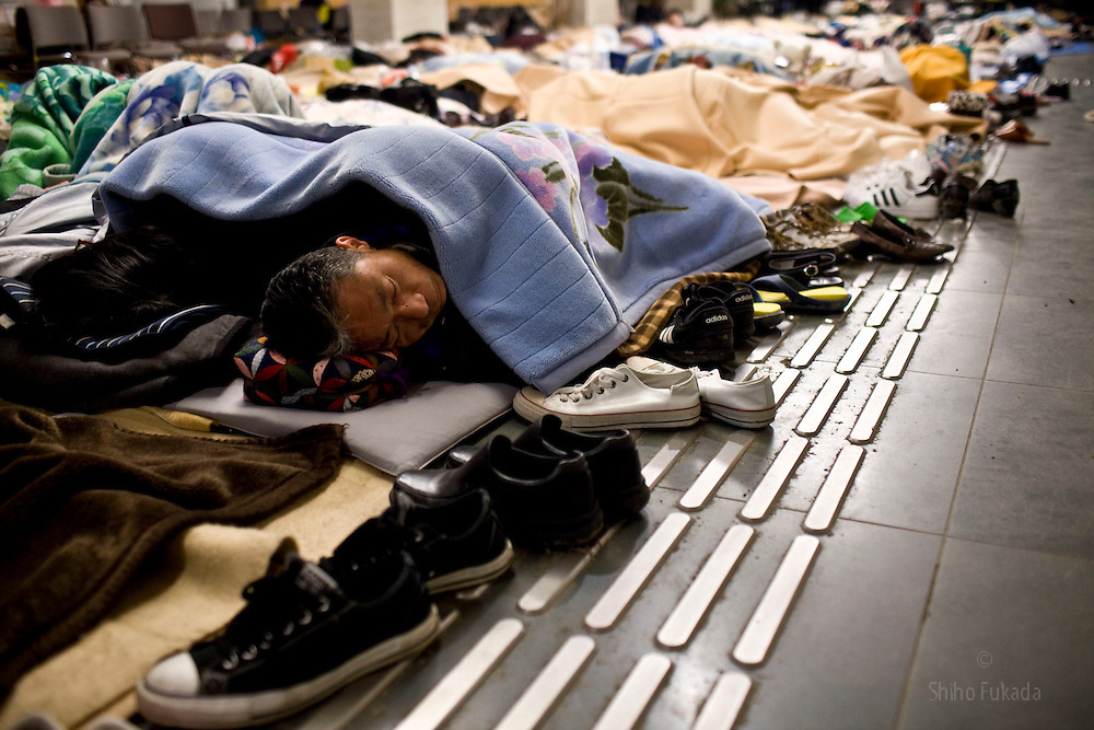 Evacuees sleep at temporary shelter at Natrori Culture Center in Miyagi, Japan, March 14, 2011. About 1000 people stay here.