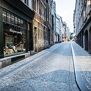 A deserted cobblestone street in the old town section of Lower Town Brussels, Belgium.