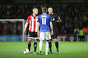 Referee Stuart Attwell talking to Cardiff City midfielder, Craig Noone (11) and Brentford defender, Jake Bidwell (3) during the Sky Bet Championship match between Brentford and Cardiff City at Griffin Park, London, England on 19 April 2016. Photo by Matthew Redman.