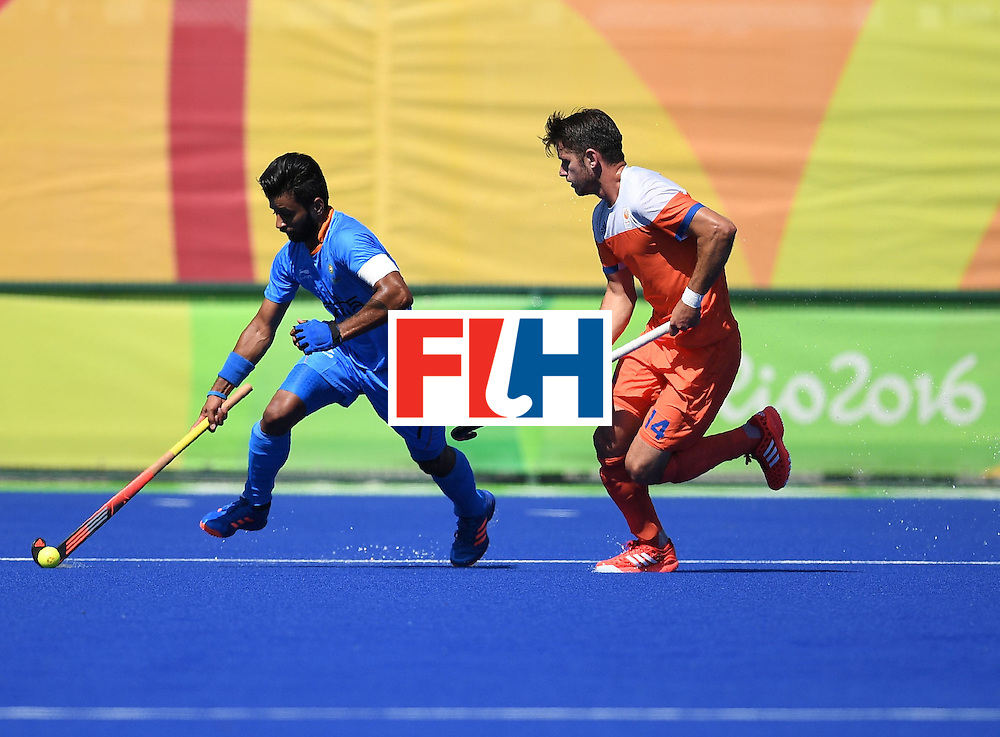 India's Manpreet Singh (L) controls the ball as Netherland's Robbert Kemperman chases during the men's field hockey Netherland's vs India match of the Rio 2016 Olympics Games at the Olympic Hockey Centre in Rio de Janeiro on August, 11 2016. / AFP / MANAN VATSYAYANA        (Photo credit should read MANAN VATSYAYANA/AFP/Getty Images)