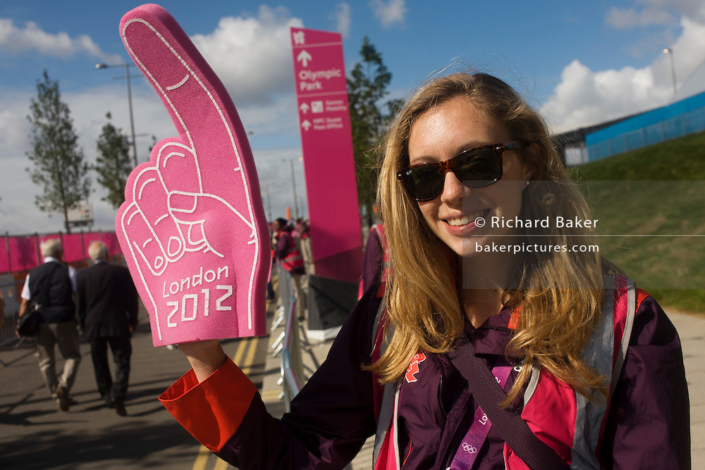 A Games Maker volunteer shows her direction hand for spectators to follow towards the London 2012 Olympic Park during the games. London 2012 volunteers are called 'Games Makers', as they are helping to make the Games happen. Up to 70,000 Games Makers take on a wide variety of roles across the venues: from welcoming visitors; to transporting athletes; to helping out behind the scenes in the Technology team to make sure the results get displayed as quickly and accurately as possible. Games Makers come from a diverse range of communities and backgrounds, from across the UK and abroad. The vast majority are giving up at least 10 days to volunteer during the Games.