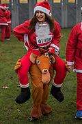 Relaxing before the start - Participants of all ages don Santa suits for the London Santa Dash on Clapham Common. The event was to raise money for the Great Ormond Street Hospital (GOSH) Children's Charity and involved a 5 or 10k run.