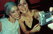 Two smiling women take a photo in Gossips club, London, U.K, 2000.