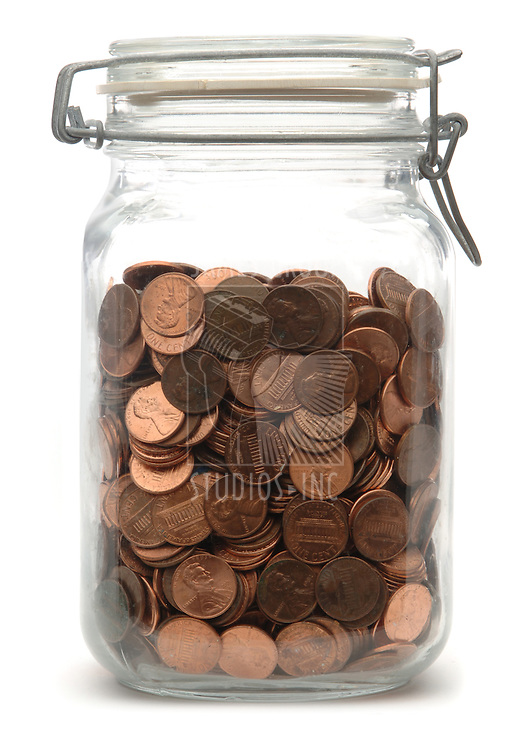 Glass jar of pennies on a white background