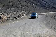 Car driving on unsurfaced road,  Jandia peninsula, Fuerteventura, Canary Islands, Spain