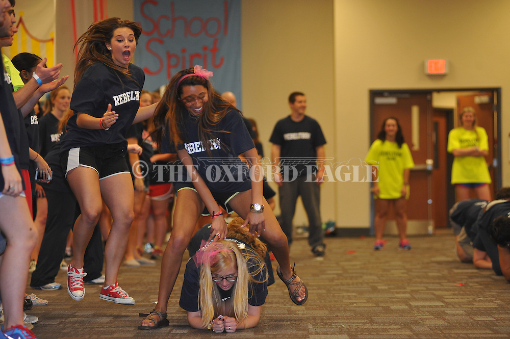 Nadisha Kaul hops over teammate Katie Knight in the leap frog race during the Rebelthon fundraiser to benefit Le Bonheur Children's Hospital in Oxford, Miss. on Friday, April 5, 2013.