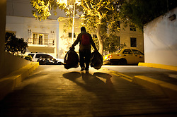 Basilio Gomez goes to work every night about 7 pm. He walks the streets of Lima searching through trash looking for plastic and glass bottles, paper, or any other item of value.