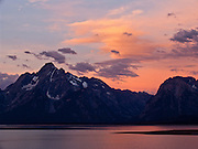 At Jackson Lake, sunrise illuminates clouds with orange, pink, and magenta light. Grand Teton National Park contains the major peaks of the 40-mile (64 km) Teton Range and part of the valley known as Jackson Hole, in Wyoming, USA. A parkway connects 10 miles north to Yellowstone National Park. Surrounding parkland and National Forest constitute the Greater Yellowstone Ecosystem, one of the largest intact mid-latitude temperate ecosystems in the world.