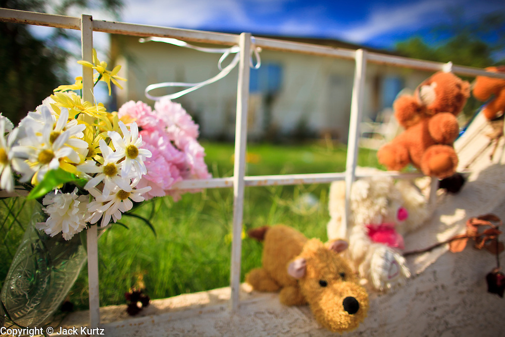"""15 AUGUST 2011 - PHOENIX, AZ: Teddy Bears and flowers on the fence in front of the home that Ame Deal, a 10 year old girl allegedly murdered by her family when she was locked in a footlocker, lived in in Phoenix, AZ. Phoenix police homicide investigators have arrested four people in connection to the death of the 10-year-old girl whose body was found inside a box on July 1, 2011. Police originally thought a game of hide-and-seek had turned deadly but now say family members fabricated the story. During the initial investigation, the family had told police that Ame Lynn Deal and other children were playing hide-and-seek and they believed that Ame must have climbed into the storage box to hide and had accidentally suffocated. According to Sgt. Trent Crump with the Phoenix Police Department, investigators determined that Ame was forced into the footlocker-type box as punishment for stealing a Popsicle from the refrigerator. The box was padlocked and Ame was left in it overnight at her home near 35th Avenue and Broadway Road. She was found dead the following morning. Crump said Ame was forced to do backbends for several hours prior to dragging the chest inside the house herself. He described the box as 31.5 inches in length, 14 inches wide and 12.25 inches deep. At the time of her death, Ame was 4 feet 2 inches tall and weighed 60 pounds. Ame's family members regularly locked her in the box as discipline for poor behavior, according to Crump. There were allegations that she was fed hot sauce, deprived of food and beaten with a board over the past few months. He said when Ame wouldn't pick up dog feces, it was rubbed on her and she was forced to eat it. """"This child died at the hands of those who were supposed to love and care for her... this case has turned the stomachs of some of our most seasoned detectives,"""" Crump said. John Allen and his wife, Samantha Allen, both 23, confessed to placing and padlocking Ame in the box on July 12. They were left in charge of Ame that n"""