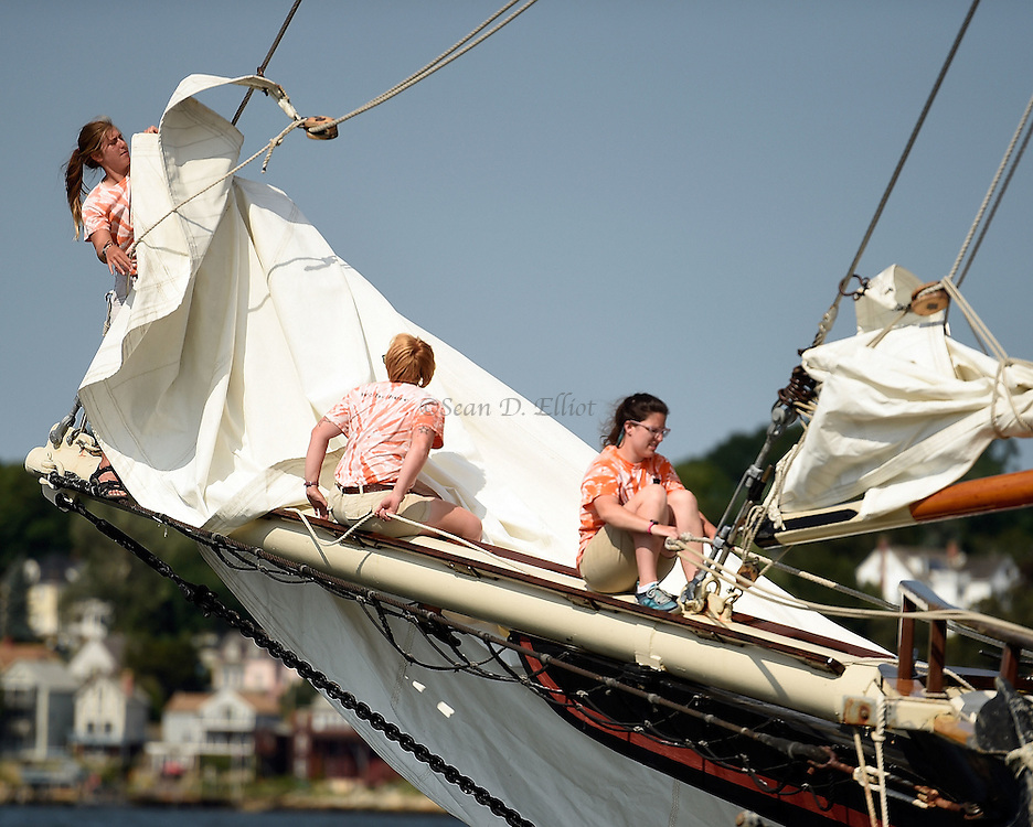 7/20/16 :: REGION :: STAND ALONE :: Deckhands on the schooner Mystic Whaler, from left, A.J. Jacobsen, Lindsay Unruh and Ann Marie Carton furl the jib following a day sailing in Long Island Sound Wednesday, July 20, 2016. The Whaler is a reproduction of a 19th century coastal cargo schooner built in Florida in 1967 and cruises from the New London waterfront six days a week. (Sean D. Elliot/The Day)