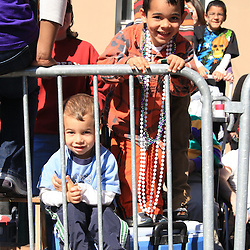 24 February 2009: Kids watch from behind barricades as floats from the Zulu parade roll along St. Charles Avenue parade route throwing beads, painted coconuts and various trinkets on Mardi Gras day in New Orleans, Louisiana. Mardi Gras is an annual celebration that ends at midnight with the start of the Catholic Lenten season which begins with Ash Wednesday and ends with Easter..