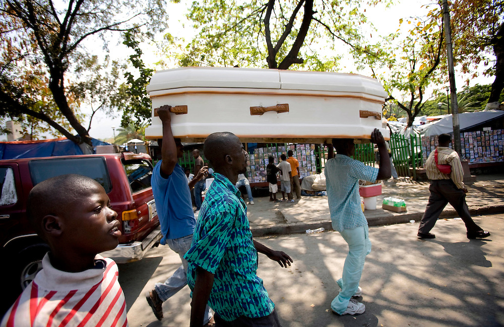 A coffin carry in the street of Purt au Prince after the earthquake in 2010..Keeping with a long tradition of Christian missionary work in Haiti, the January 2010 earthquake brought huge numbers of Christian organizations to the country to help the devastated population with food, shelter and spiritual guidance. But the earthquake has had another, less obvious impact. Haiti has a large traditional Voodoo population. Some evangelical Christian groups not only dismiss the Voodoo religion as a Satanic cult, but in fact blame practitioners for the earthquake, saying it was God's punishment. Voodoo spiritual leaders say this belief has led to disparate treatment of earthquake victims by Christian aid groups, with Christian converts getting better tents and food, and Voodoo congregations left unattended. The tension has erupted into violent clashes and attacks on Voodoo temples in Carrefour and Cité Soleil. Voodoo leaders say missionaries are using the promise of food and medical supplies to lure people to religious meetings to convert them and complain international aid is only going to Christian groups.