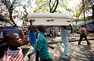A coffin carry in the street of Purt au Prince after the earthquake in 2010..Keeping with a long tradition of Christian missionary work in Haiti, the January 2010 earthquake brought huge numbers of Christian organizations to the country to help the devastated population with food, shelter and spiritual guidance. But the earthquake has had another, less obvious impact. Haiti has a large traditional Voodoo population. Some evangelical Christian groups not only dismiss the Voodoo religion as a Satanic cult, but in fact blame practitioners for the earthquake, saying it was God's punishment. Voodoo spiritual leaders say this belief has led to disparate treatment of earthquake victims by Christian aid groups, with Christian converts getting better tents and food, and Voodoo congregations left unattended. The tension has erupted into violent clashes and attacks onVoodoo temples in Carrefour and Cité Soleil. Voodoo leaders say missionaries are using the promise of food and medical supplies to lure people to religious meetings to convert them and complain international aid is only going to Christian groups.