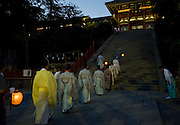 Priests walk through the shrine grounds during the annual Reitaisai Grand Festival at Tsurugaoka Hachimangu Shrine in Kamakura, Japan on  14 Sept. 2012.  Sept 14 marks the first day of the 3-day Reitaisai festival, which starts early in the morning when shrine priests and officials perform a purification ritual in the ocean during a rite known as hamaorisai and limaxes with a display of yabusame horseback archery. Photographer: Robert Gilhooly