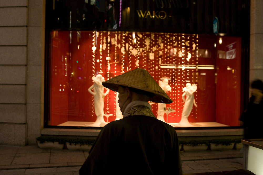 Christmas lights in Tokyo's Ginza district..Monk collecting money stands in front of store, Holiday windowdisplay