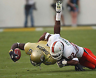 Georgia Tech's Calvin Johnson is tackled by a University of Miami football player.  2006 © Johnny Crawford