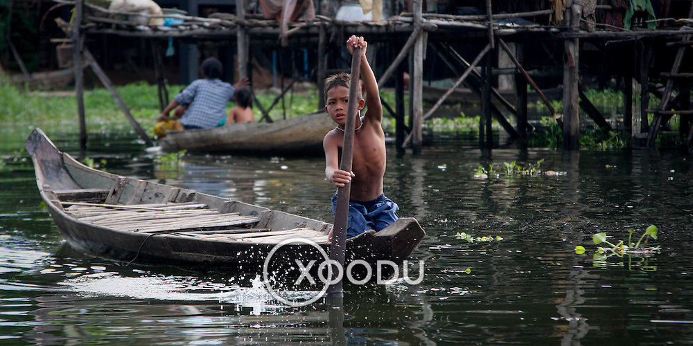 Young boy in canoe amidst wooden fishing village stilt houses (Siem Reap, Cambodia - Oct. 2008) (Image ID: 081023-1634231a)