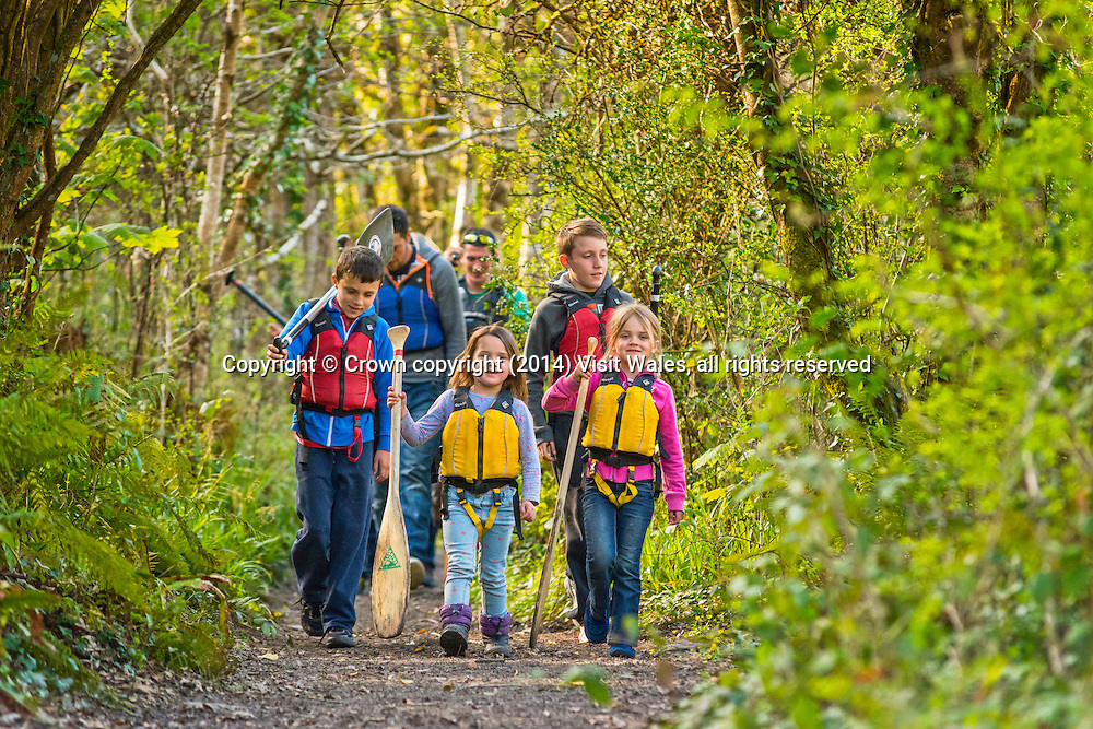 Family kitted up and walking along path through wood to river<br /> River Canoeing<br /> River Teifi<br /> Cilgerran Gorge<br /> Ceredigion<br /> Mid<br /> Water Sports<br /> Activities and Sports