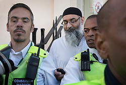 © Licensed to London News Pictures. 19/10/2018. London, UK. Radical preacher ANJEM CHOUDARY is seen looking at a mobile phone as stands outside a bail hostel after being released form Belmarsh Prison in south-east London. Photo credit: Peter Macdiarmid/LNP