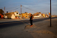 A woman stands on a street corner on Friday, Apr. 10, 2009 south of Lima, Peru.