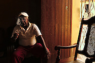 Man smoking a cigar inside his house in Trinidad.