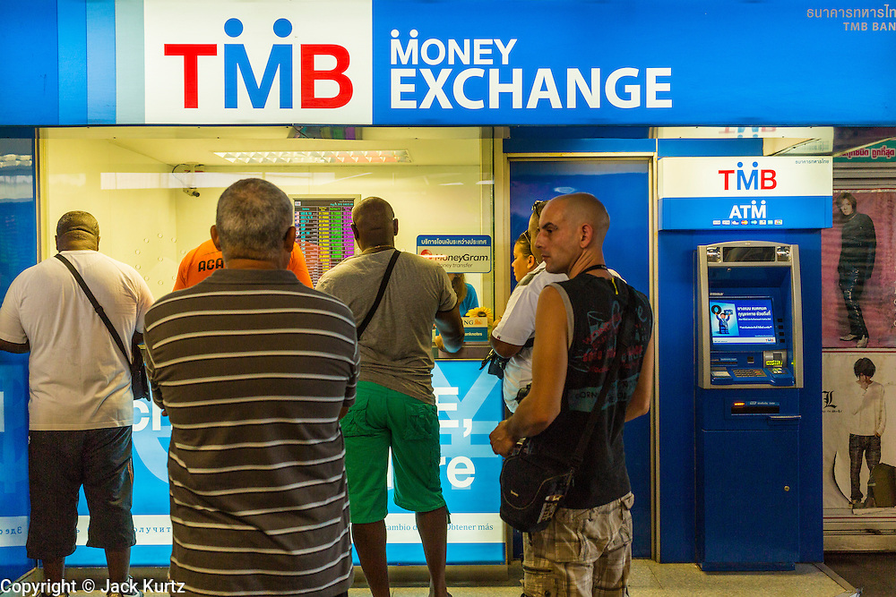 """24 AUGUST 2013 - BANGKOK, THAILAND: Tourists line up to buy Thai Baht at a money exchange booth in Bangkok. Thailand entered a """"technical"""" recession this month after the economy shrank by 0.3% in the second quarter of the year. The 0.3% contraction in gross domestic product between April and June followed a previous fall of 1.7% during the first quarter of 2013. The contraction is being blamed on a drop in demand for exports, a drop in domestic demand and a loss of consumer confidence. At the same time, the value of the Thai Baht against the US Dollar has dropped significantly, from a high of about 28Baht to $1 in April to 32THB to 1USD in August.     PHOTO BY JACK KURTZ"""