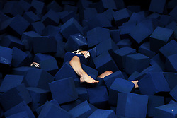 Annalee Wilson, 18, of Lyme struggles out of a pit of foam cubes after slipping off the bar while practicing giants at Northern Lights Gymnastics in Wilder, Vt., Monday, July 28, 2014.<br /> (Valley News - James M. Patterson)