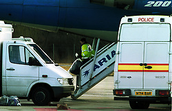 Police checking the Ariana Afghan Airlines plane on the tarmac, the hijack ended early this morning, February 10, 2000. Photo by Andrew Parsons / i-images..