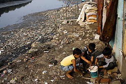Children play along the dirty banks of a polluted river in a slum in Mumbai.  TB disproportionately affects the poor.