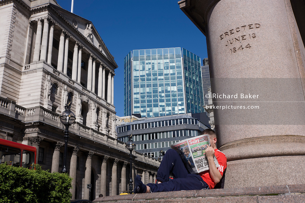 A Sun newspaper reader below a statue at Bank Triangle, with the Bank of England to the left.