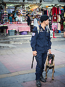 24 AUGUST 2015 - BANGKOK, THAILAND: A Thai policeman with his bomb sniffing dog in central Bangkok. One week after the a bomb at the Erawan Shrine in the center of Bangkok killed dozens and hospitalized scores of people, police have not made any arrests. Police bomb sniffing dogs have been deployed to malls and markets around Bangkok. There was a large memorial service sponsored by businesses close the bomb site Monday evening.     PHOTO BY JACK KURTZ