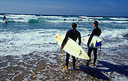 Two surfers holding their surf boards looking out to sea Fistral beach Newquay UK May 2002