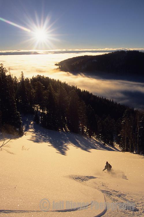 A backcountry skier makes tracks through powder snow at sunrise on Teton Pass in Jackson Hole, Wyoming.