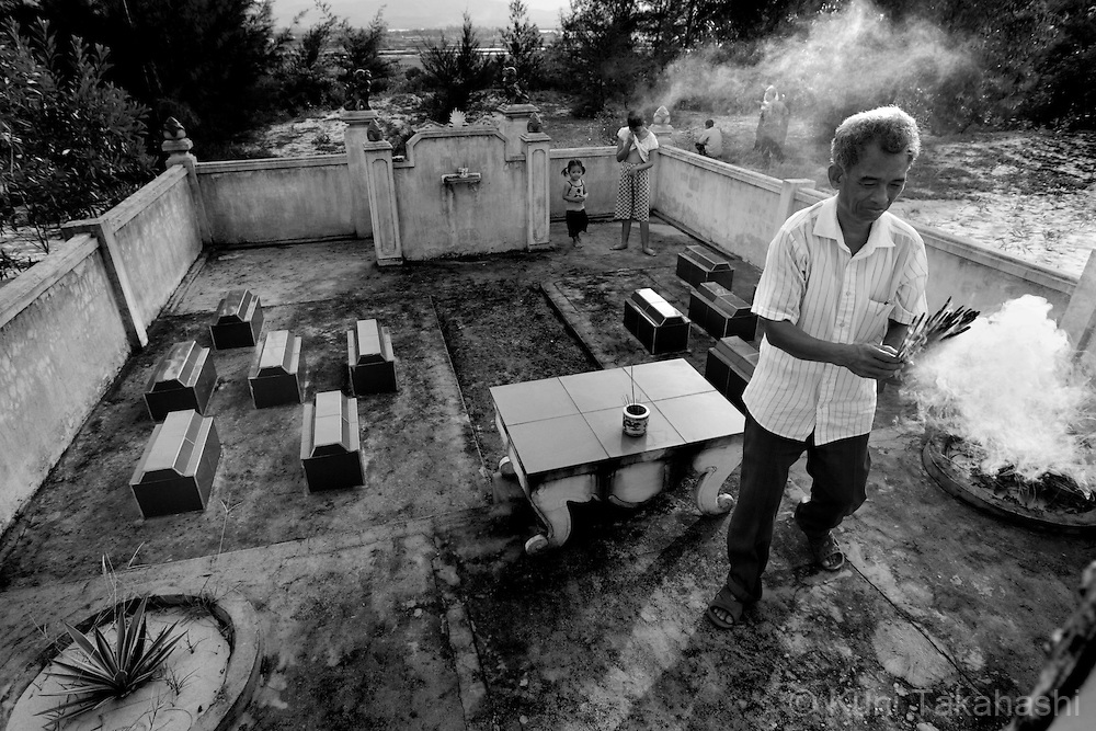 Do Duc Diu, 58, visits his family grave with his daughter Do Thi Nga, 15, near their house in Quang Binh Province in northern Vietnam on June 25, 2009. Diu, who served in the army in A Shau Valley and was sprayed upon directly countless times, lost 12 of his 15 children before they turned three years old. Two of his existing daughters have health problems - one has fluid in the brain and the other has cerebral palsey-like symptoms..