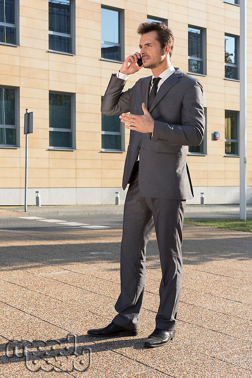 Full length of businessman using cell phone against office building