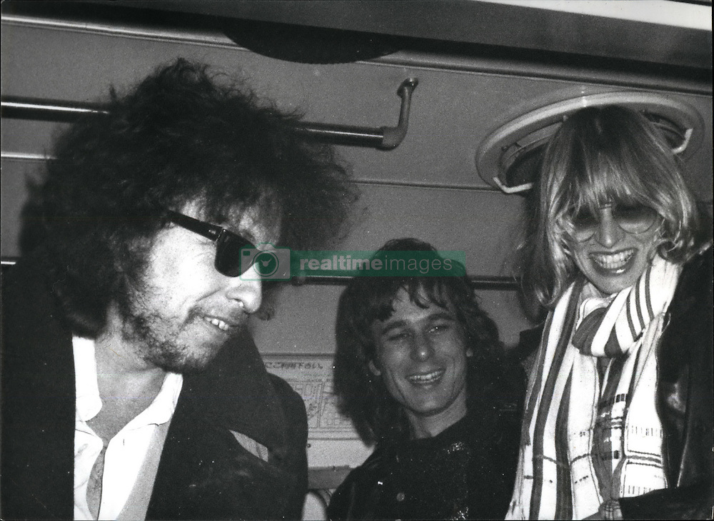 May 05, 1978 - Tokyo, Japan - Just off the plane at Tokyo's haneda airport Bob Dylan and members of his band, who flew in from Los Angeles for their first ever concert-tour of Japan,l found themseleves the target of a large group of Japanese photographers, some of whom had braved the chilly winds on the airfield for several hours. Safely inside the waiting bus, Dylan & Co. paused for a smile - before heading to a press-conference at an airport hotel, which was jammed by more than 150 press people and journalists. Asked to define the term love, Dylan replied: ''The ability to reason''. He also stated that he might debut new song-material while in Japan and called his eralier protest-songs his ''most brilliant love songs.'' Bob Dylan is scheduled to give 10 concert appearances in Tokyo and Osaka. (Credit Image: © Keystone USA via ZUMAPRESS.com)