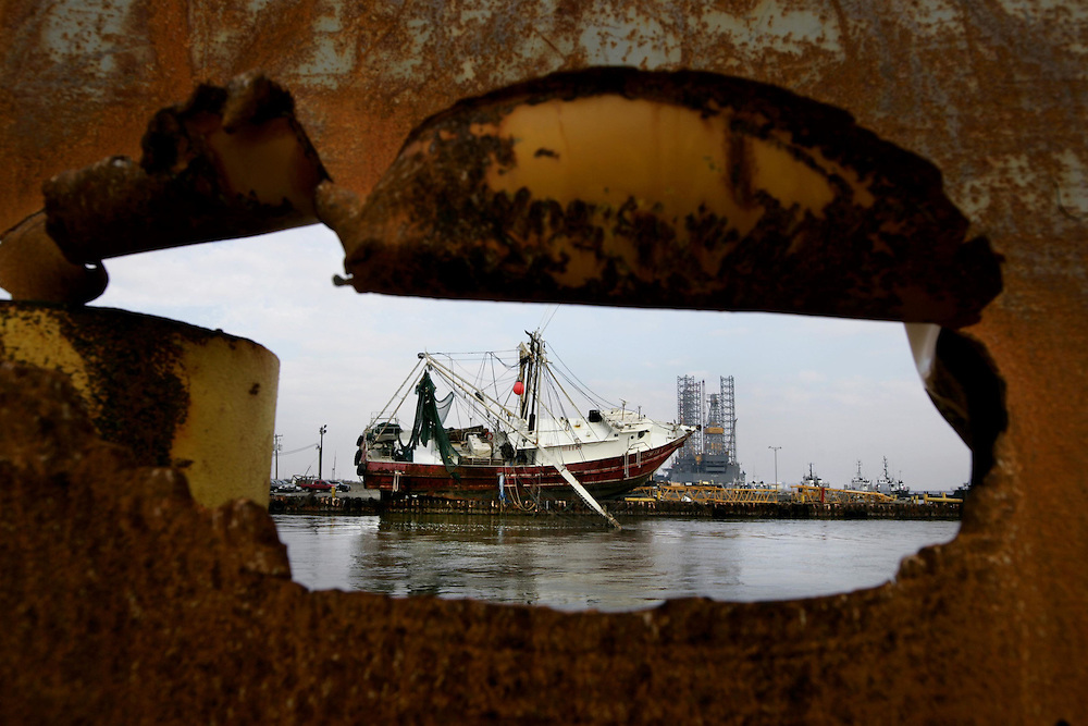 A shrimp boat sits atop debris on a dock where it was washed during Hurricane Ike Friday September 19, 2008.  (seen through a hole in a dumpster that was damaged by the storm on the RRB Dock Services, LLC, dock)