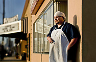 A male line cook having a cigarette break outside the restaurant that employees him