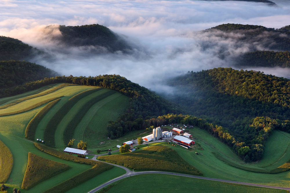 Aerial of farmland in southwest Wisconsin near the Mississippi River, south of La Crosse.  Farms surrounded by clouds along the ridges of the rich Loess bluffs along the Mississippi River.