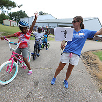 Susan Daughdrill, right. shows the correct way to signal a right turn while riding a bicycle as part of the CATCH Kids bike rodeo held Thursday at the Haven Acres Boys & Girls club.