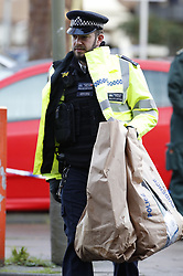 © Licensed to London News Pictures. 06/02/2019. London, UK. A police officer carries evidence bags from the crime scene on Westbridge Road in Battersea after a 19 year old man was fatally stabbed last night. Police have arrested two men. Photo credit: Peter Macdiarmid/LNP