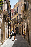 Locals in street scene in alleyway in Greek Streets by via Della Giudecca, Ortigia, Syracuse, Sicily