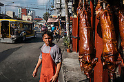 Lechon, roasted pigs, sit out on the street ready for sale in La Loma, part of Metro Manila, Philippines. If all the pig isn't consumed, the leftovers are cooked in vinegar to become paksiw na lechon, another popular sour dish.