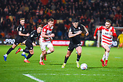 Alex Mowatt of Barnsley (27) escapes a group of players including Alfie May of Doncaster Rovers (19) during the EFL Sky Bet League 1 match between Doncaster Rovers and Barnsley at the Keepmoat Stadium, Doncaster, England on 15 March 2019.