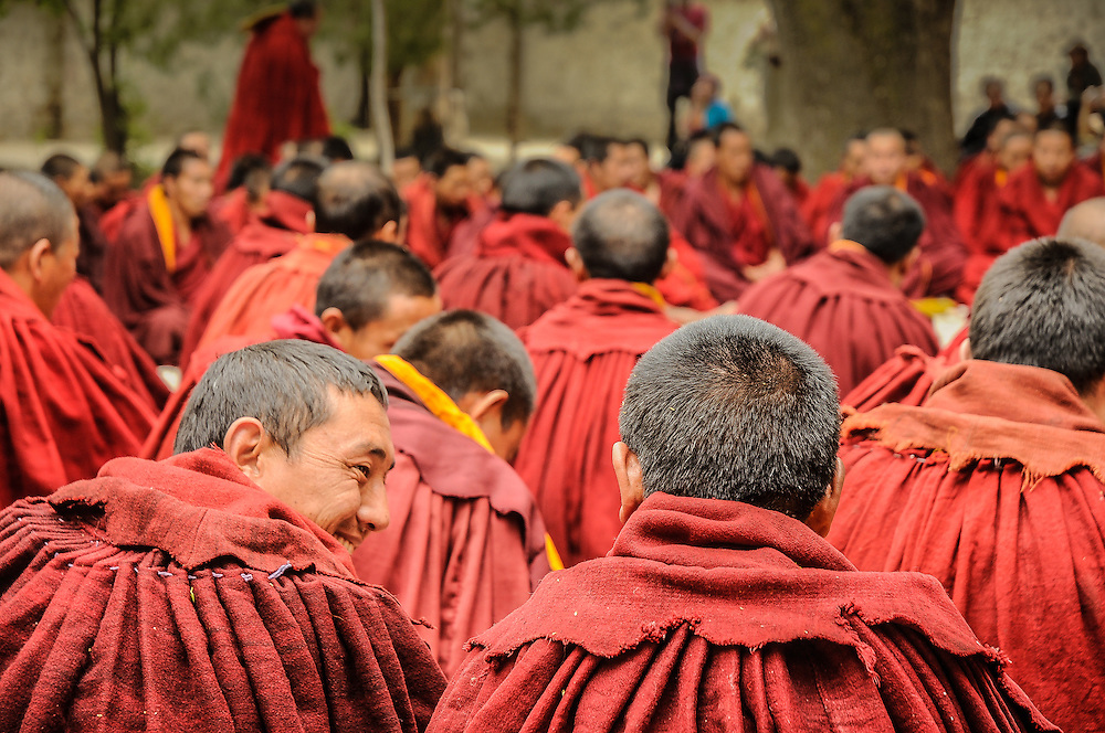 Group of monks sitting on the floor after Debate, one in laughing, Sera monastery, Lhasa, Tibet.