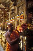 Monk standing by inner shrine room of the Dalada Maligawa in kandy.