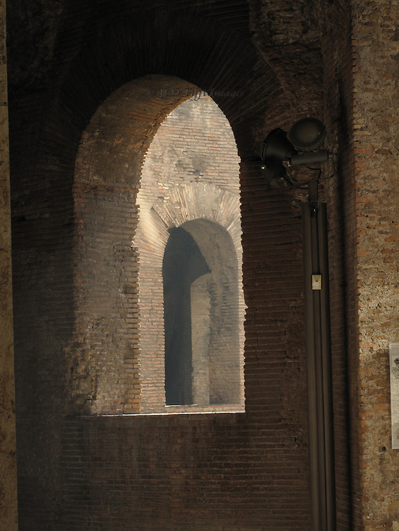Sequence of empty arched windows piercing walls of Trajan's Markets, Rome.  Closeup of one, beyond which two more in sequence can be seen.