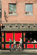 Pedestrians pass the Village Idiot Pub on Toronto's Dundas Street West.