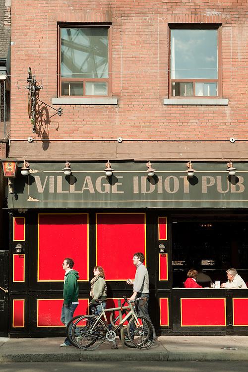 Pedestrians pass the Village Idiot Pub on Toronto's Dundas Street West.